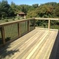 Pressure-treated deck with 5x5 railing posts and black rod railing
