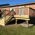 Pressure-treated deck with black rod railing
